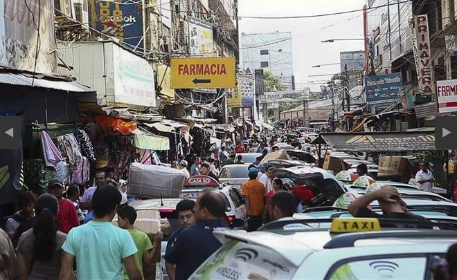 """Cidade Del Este virou referência em TV pirata mundial: por lá as """"marcas"""" patrocinam lojas e até têm outdoors na cidade."""
